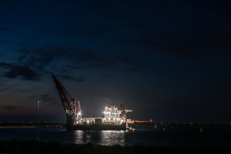 Illuminated commercial dock by sea against sky at night