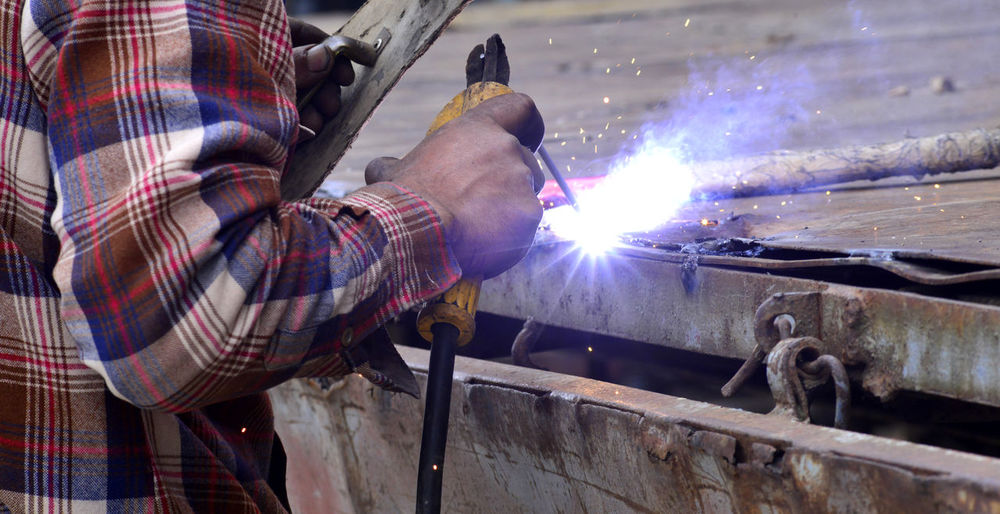 Midsection Of Man Welding In Workshop