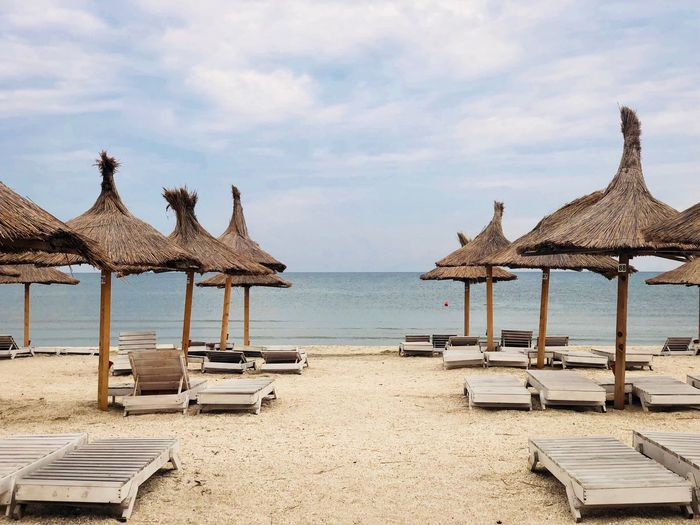 Lounge chairs and thatched roofs at beach against sky