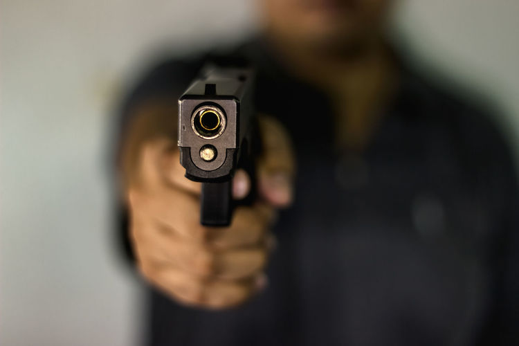 Close-Up Of Man Aiming Gun Against Blurred Background