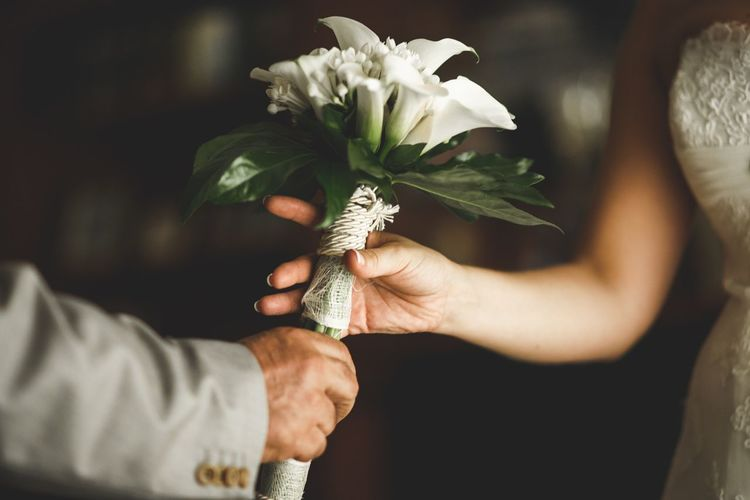 Cropped hand of bridegroom giving bouquet to bride