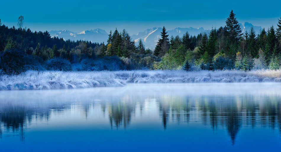 Beauty In Nature Cold Temperature Distant Geometry Horizontal Symmetry Lake Lakeshore Majestic Mountain Mountain Range Reflection River Scenics Snow Standing Water Symmetry Tranquil Scene Tranquility Tree Water Waterfront Winter Landscapes With WhiteWall