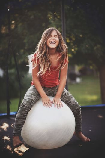 Smiling girl sitting over fitness ball on trampoline