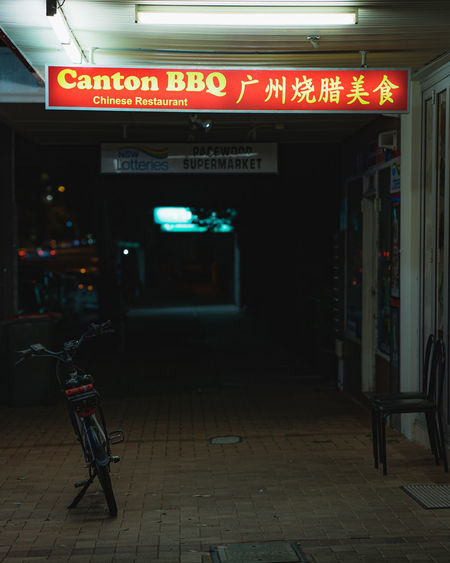 Illuminated text on footpath by building at night