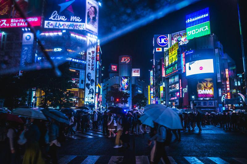 People On Illuminated Street During Rainy Season At Night