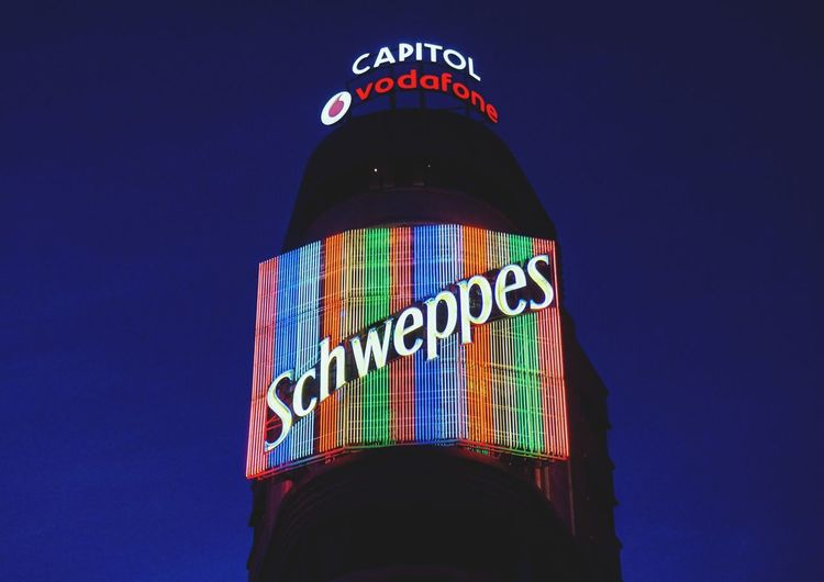 Low angle view of illuminated sign against blue sky
