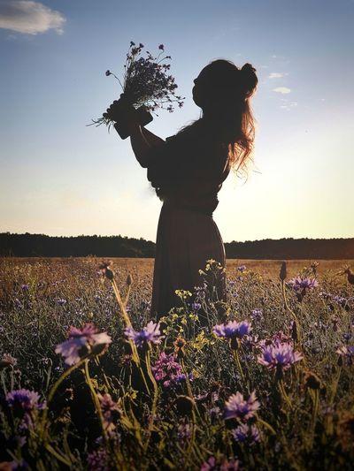 Woman standing by purple flowers on field against sky