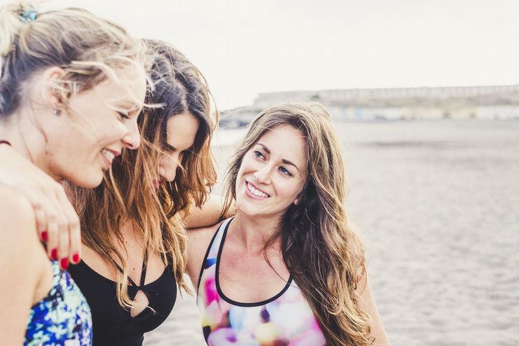Happy friends wearing bikini while enjoying together at beach
