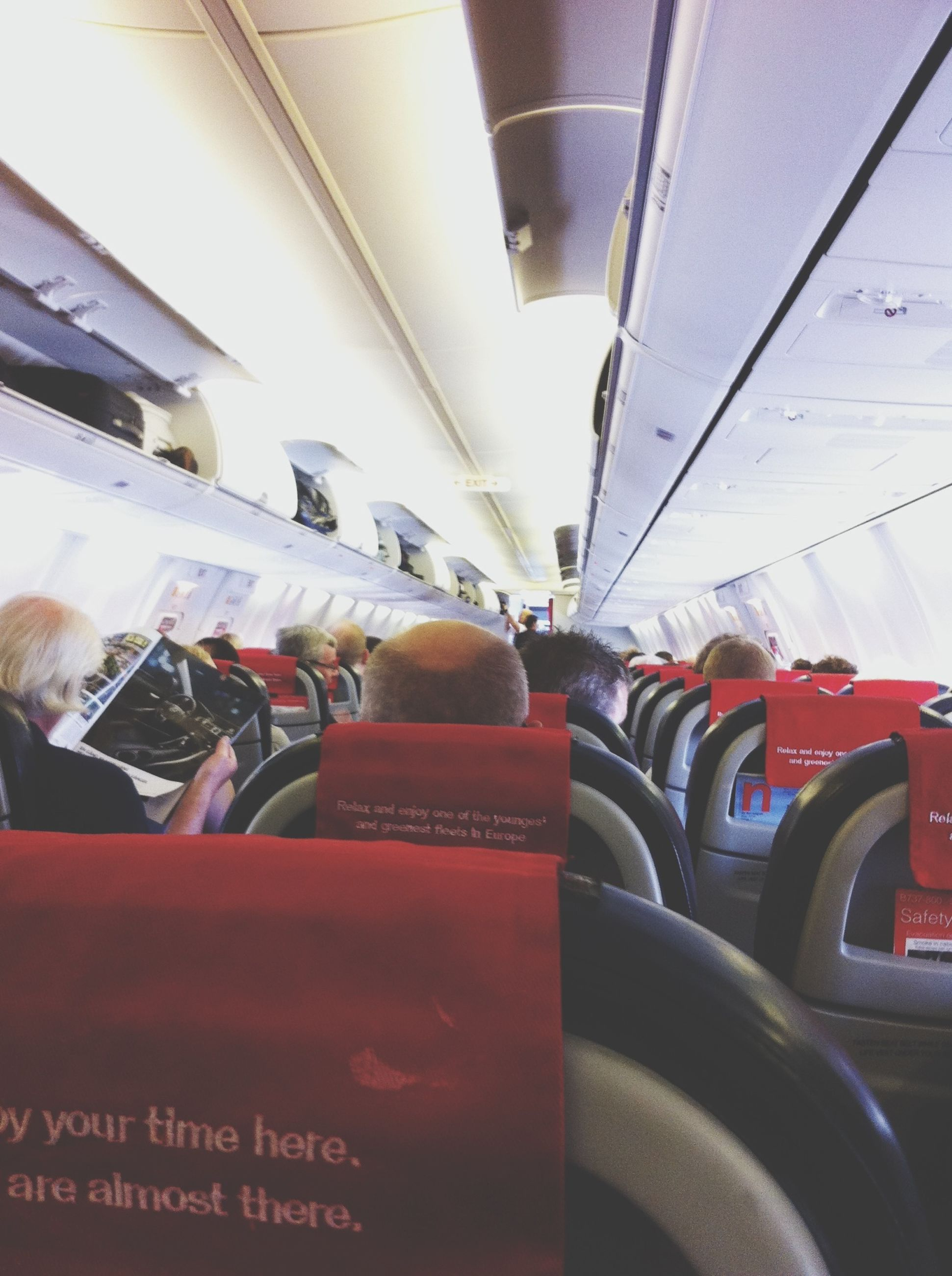 indoors, transportation, in a row, vehicle seat, vehicle interior, mode of transport, seat, public transportation, travel, red, large group of objects, train - vehicle, illuminated, order, journey, choice, incidental people, arrangement, side by side, abundance