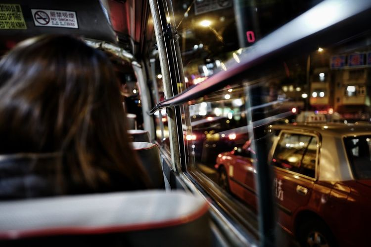 Rear view of woman traveling in bus at night