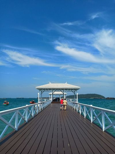 Rear view of couple walking on pier over sea