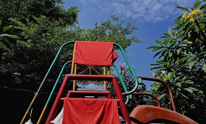 Rear view of red deck chairs against blue sky