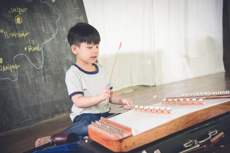 Boy Playing Yangqin Against Blackboard