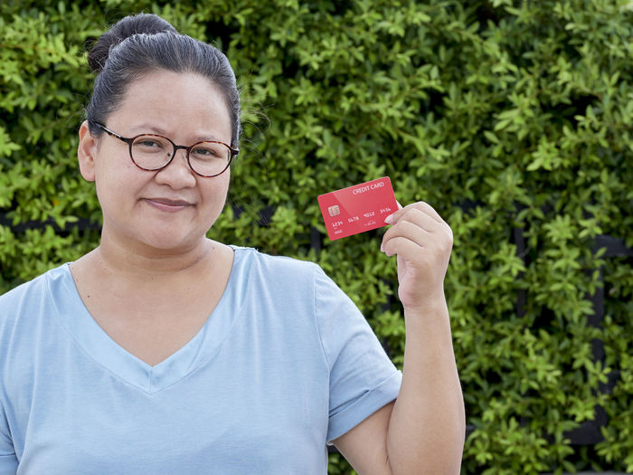 Portrait of woman holding credit card against trees