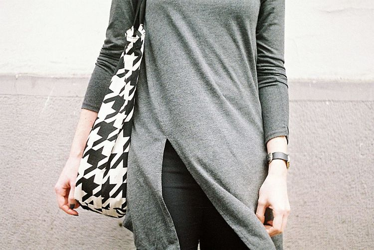 Midsection of woman with shoulder bag standing against wall