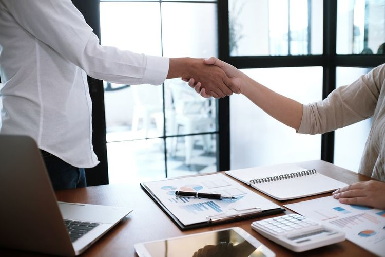 Midsection of businesswomen shaking hands in office