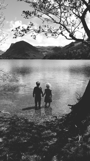 Friends standing in lake against mountains