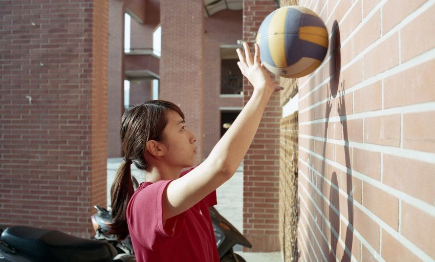 Side view of young woman playing with ball on wall