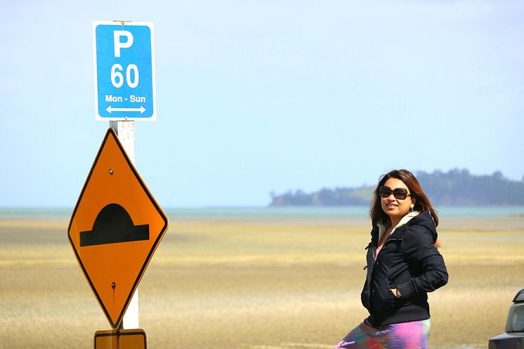 Woman Standing By Road Signs Against Sky