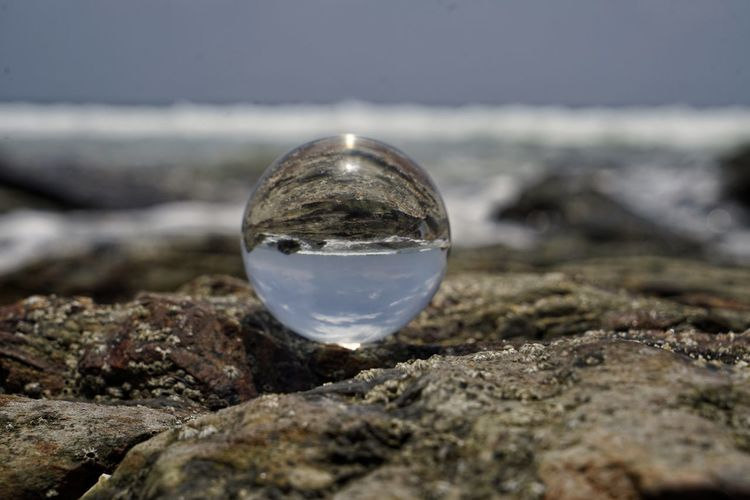 Water Glass - Material Nature Sphere Close-up Day No People Transparent Crystal Ball Selective Focus Rock - Object Solid Rock Outdoors Land Sky Focus On Foreground Reflection Beach