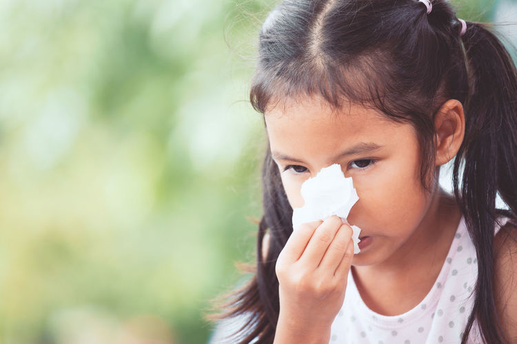 Girl wiping nose with tissue paper