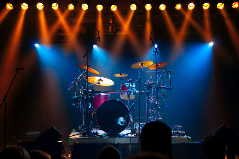 Drum Set on stage, illuminated by stage lights Arts Culture And Entertainment Concert Crowd Drum Drum - Percussion Instrument Drum Kit Enjoyment Event Illuminated Light Light - Natural Phenomenon Lighting Equipment Live Event Music Music Festival Musical Equipment Musical Instrument Musician Nightlife Performance Popular Music Concert Rock Music Stage Stage - Performance Space Stage Light