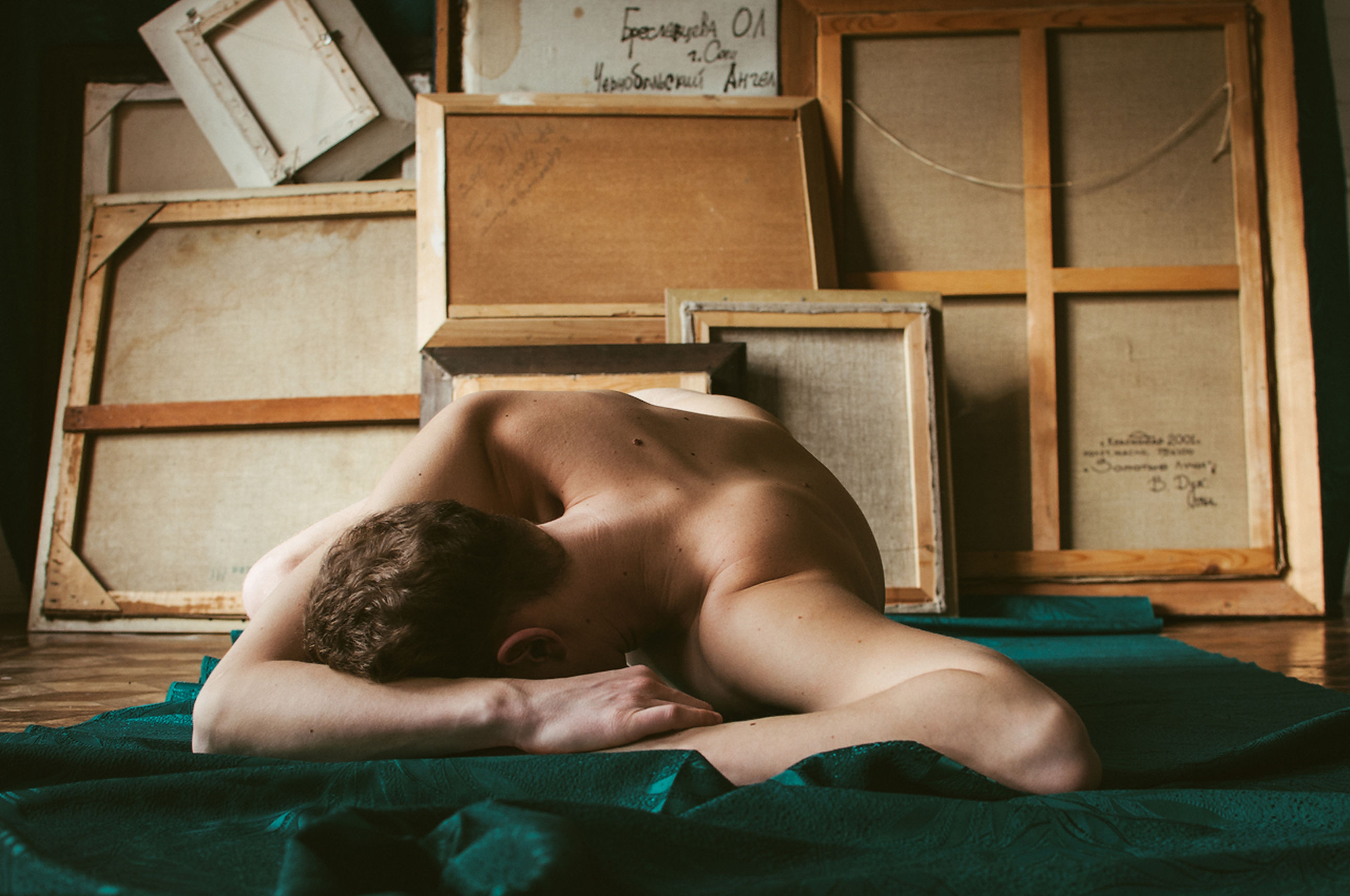 Naked man lying by picture frames