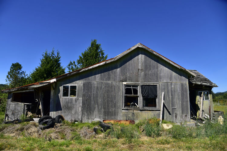 Dilapidated House Lonely Oregon Abandoned Aged Architecture Blue Building Exterior Built Structure Clear Sky Day Deep Blue Faded Faded Wood Grass Nature No People Old Buildings Old House Old Tires Outdoors Overgrowth Sky Tree