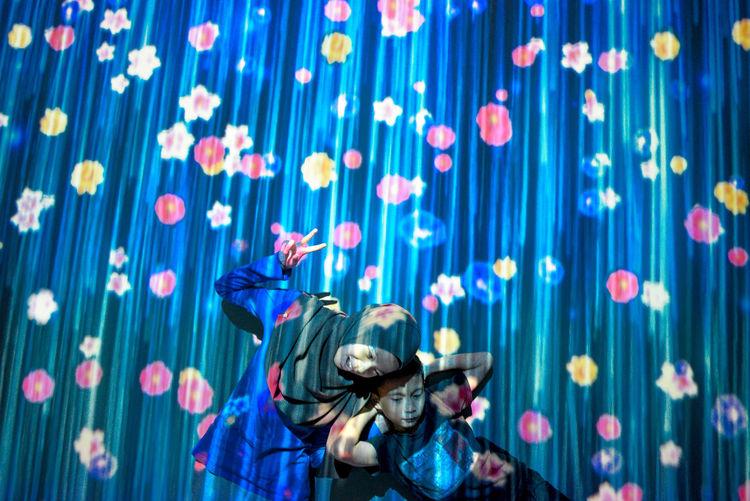Playful siblings against blue curtain