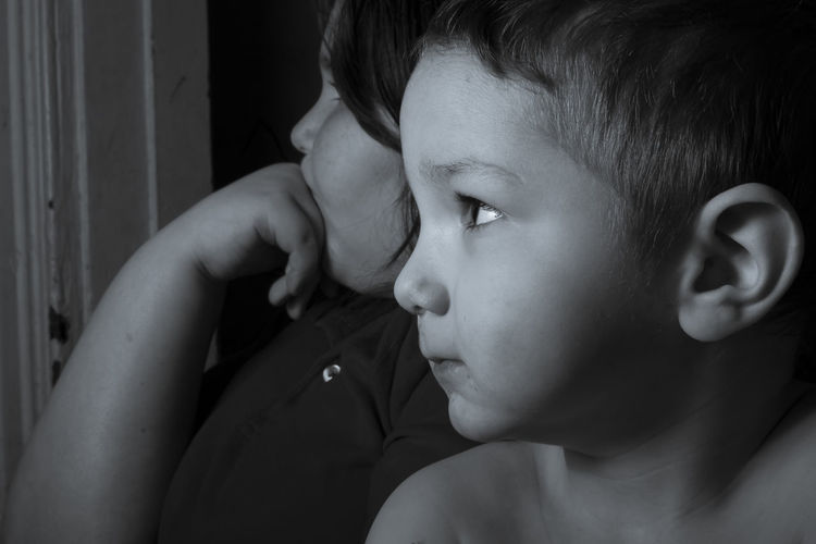 Close-up of boy with sister looking away