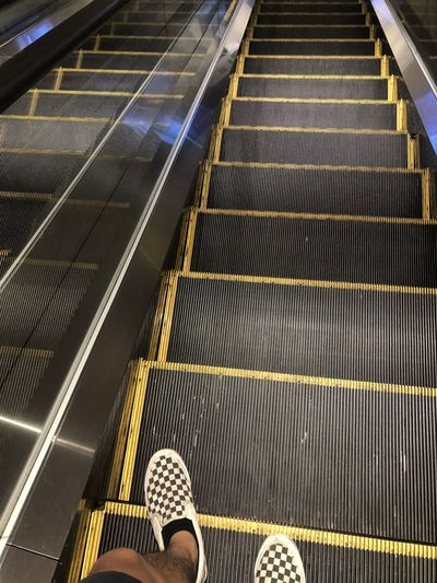 Low section of person on escalator