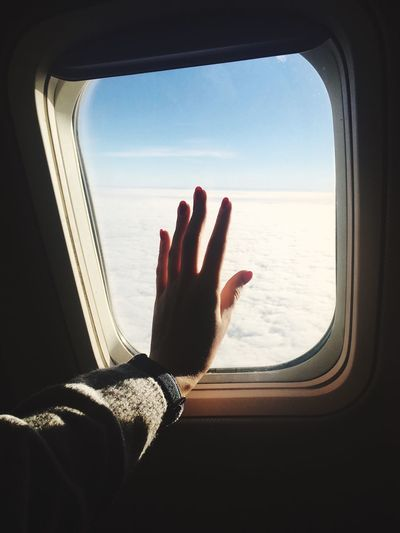 Cropped Image Of Hand  On Airplane Window