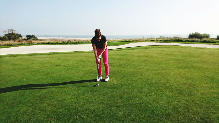 Full Length Of Woman Playing Golf On Field Against Clear Sky