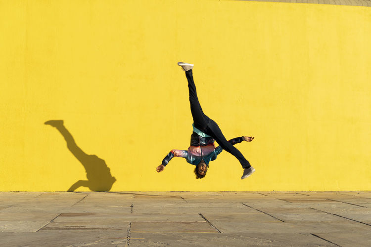 Full length of man jumping against yellow wall