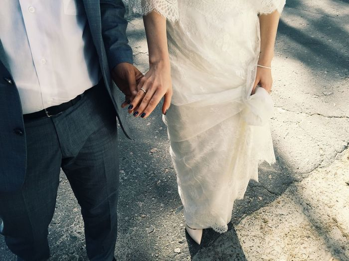 Low section of bride and groom holding hands while standing on street