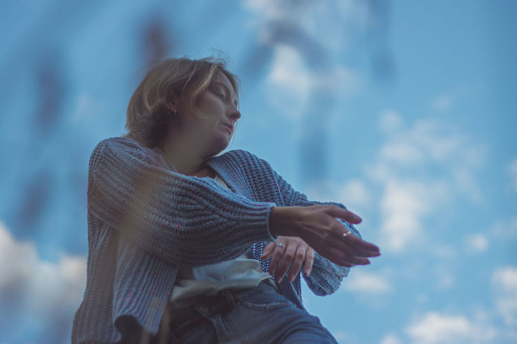 Low angle view of woman dancing against sky