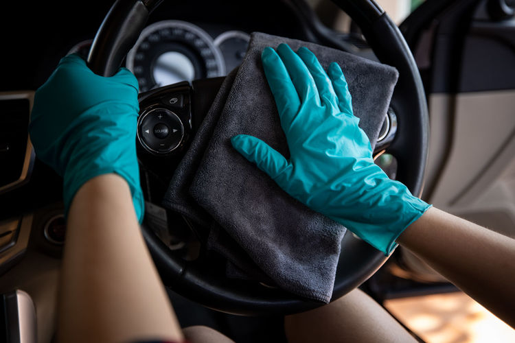 Women wearing green gloves cleaning steering wheel car with micro fiber gray cleaning car concept