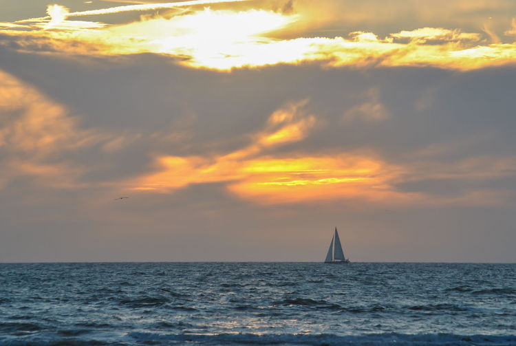 Sailboat in sea against sky during sunset