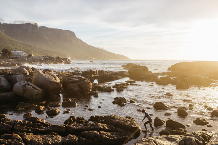Wading Out. Taken during an icy dip in Bakoven's chilly waters. Mid December, 2016. Water Rock Solid Rock - Object Sea Sky Beauty In Nature Scenics - Nature Land Beach Nature Cloud - Sky Tranquility Mountain Idyllic Outdoors Beauty In Nature Beauty Ocean Wetsuit Jonnynichayes Cape Town South Africa Bakoven Swimming My Best Photo Travel Wonder Sunset Sunset_collection Rocks And Water Explore Adventure Wanderlust Orange Color