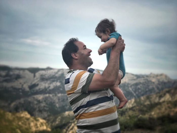 Side view of happy man carrying baby while standing against mountains