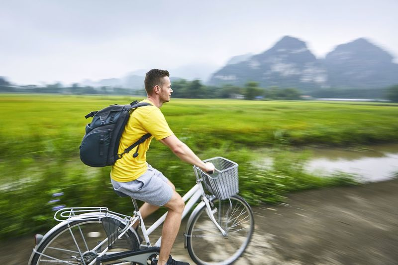 Side view of man riding bicycle by landscape on road