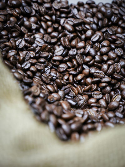 Close-up of roasted coffee beans in sack in store