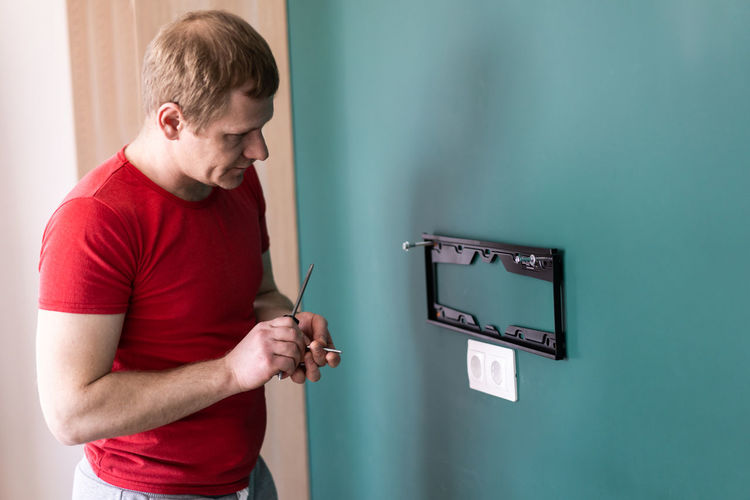 Side view of young man standing against wall