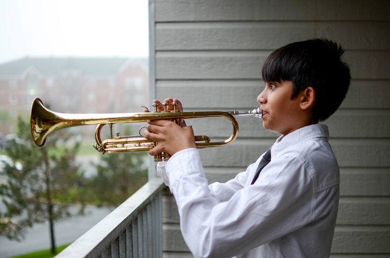 Side view of boy playing musical instrument while standing by railing