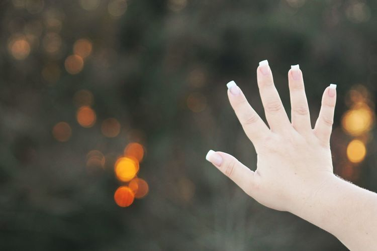 Close-up of woman hand showing her fingernails outdoors