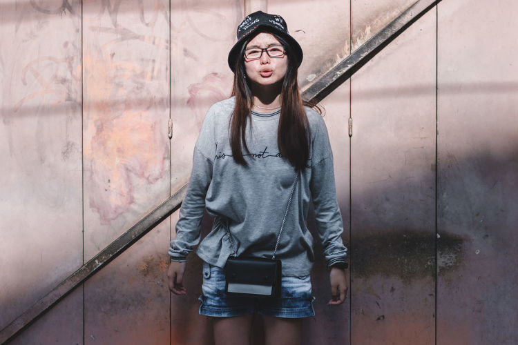 One Person Real People Front View Young Adult Lifestyles Casual Clothing Leisure Activity Standing Portrait Wall - Building Feature Clothing Young Women Looking At Camera Architecture Three Quarter Length Day Outdoors Built Structure Hairstyle Hood - Clothing Beautiful Woman Teenager Contemplation