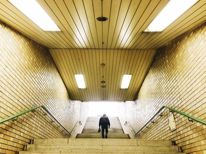 Rear view of man walking on illuminated steps at subway station