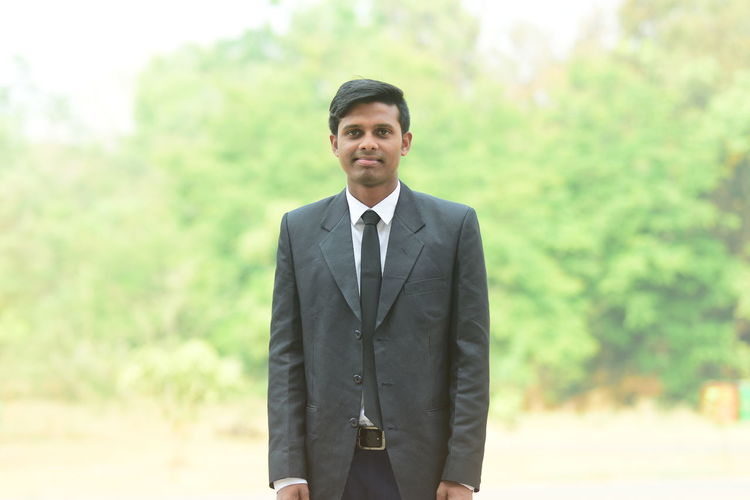 Portrait of young man wearing suit standing outdoors