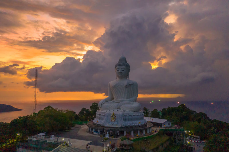 scenery sunset on Phuket big Buddha thunderstorm in sunset at Phuket big Buddha have beautiful color in the sky Phuket Big Buddha Sunset, Storm, Religion, Church, Sect, Denomination, Belief, Ideology, Creed, Teaching, Doctrine, Moslem, Islam, Statue, Statue's, David, Florence Tourism, Sky Cloud - Sky Sunset Human Representation Sculpture Statue Art And Craft Representation Religion Male Likeness Belief Architecture Built Structure Spirituality Nature Water Building Orange Color No People Idol