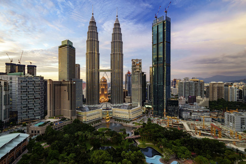 An evening in Kuala Lumpur, Malaysia Suria KLCC Architecture Building Exterior Built Structure City Cityscape Cloud - Sky Day Growth High Angle View High Rise Building Maxis Tower Modern Outdoors Petronas Twin Towers Sky Skyscraper Tall - High Tower Travel Destinations Tree Twin Towers Urban Skyline